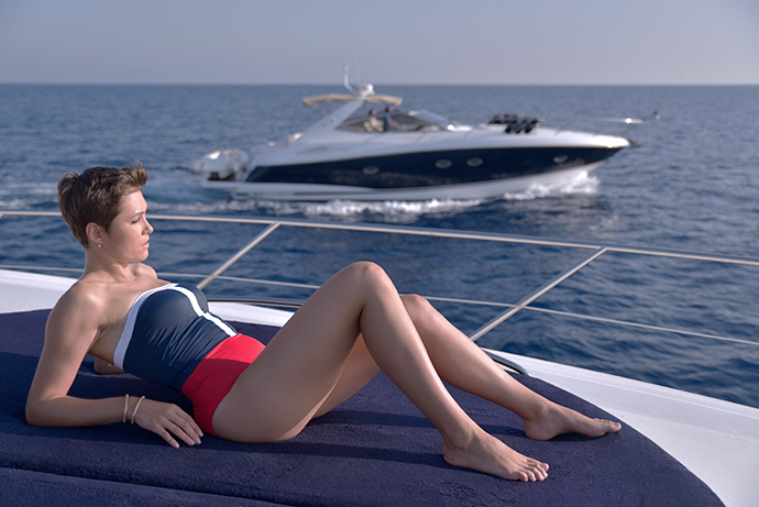 Woman sunbathing on deck aboard a luxury Sunseeker motor yacht