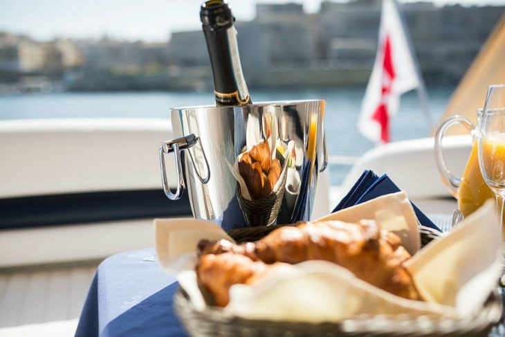 bottle of champagne and croissants served on a Sunseeker yacht
