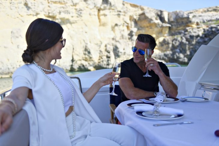couple toasting on a luxury yacht in the Mediterranean