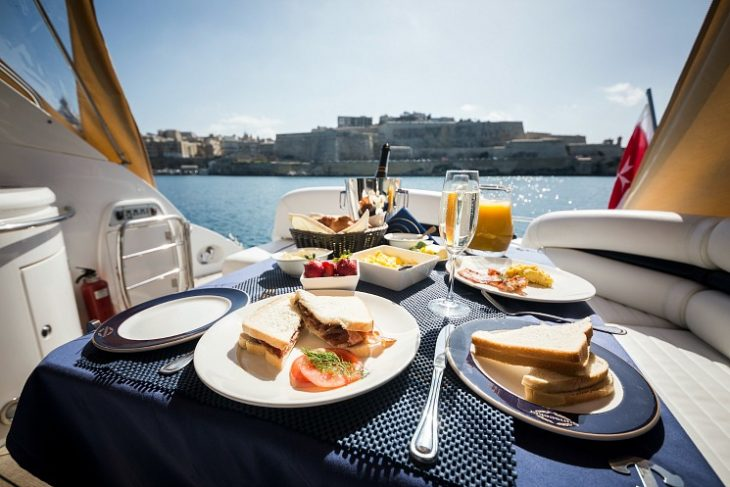 breakfast spread served on the deck of a luxury yacht