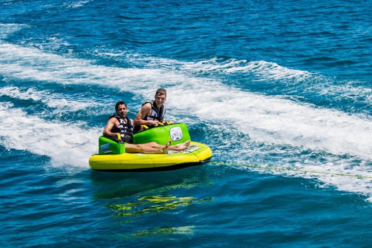 young men enjoying donut ride watersports in the Mediterranean