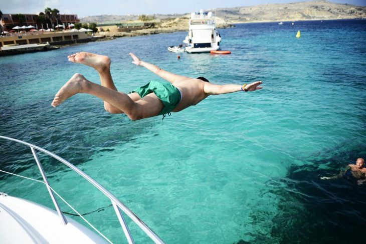 man jumping from a luxury yacht into the Mediterranean Sea
