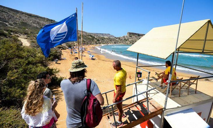 Blue flag and coast guards on Għajn Tuffieħa Bay in Malta