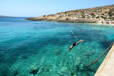 Man diving into the azure waters of Hondoq ir-Rummien Gozo