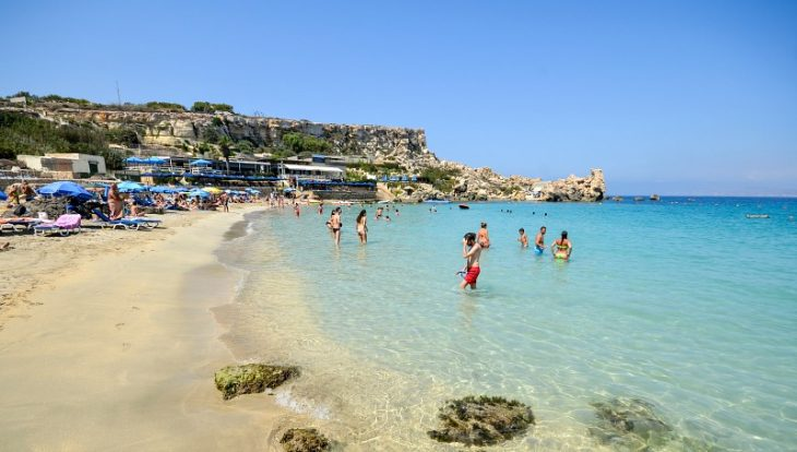 People bathing in the azure waters of Paradise Bay in Malta