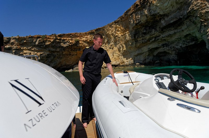 Motor yacht captain inspects jet rib tender attached to Sunseeker yacht