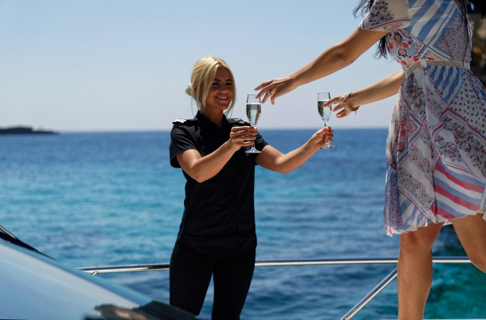 Stewardess serving champagne to guests on board a Sunseeker