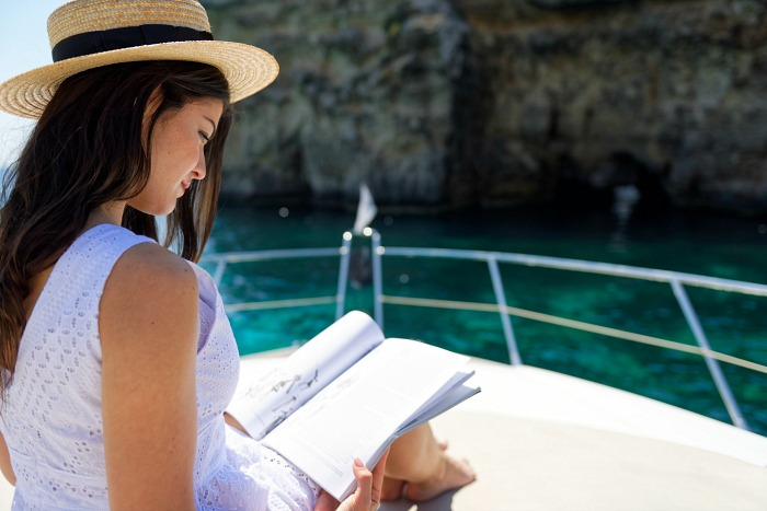 woman reading on a luxury Sunseeker yacht in the Mediterranean