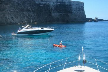 woman kayaking with luxury charter yachts in view