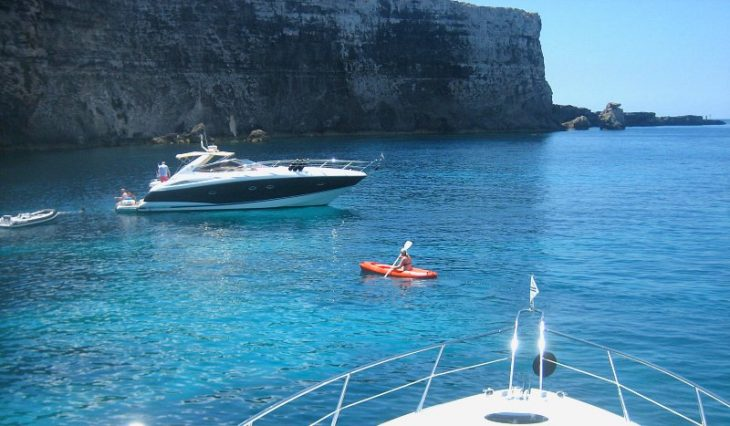 woman kayaking with luxury charter yachts in view| Why Malta is the no. 1 country for boat charter