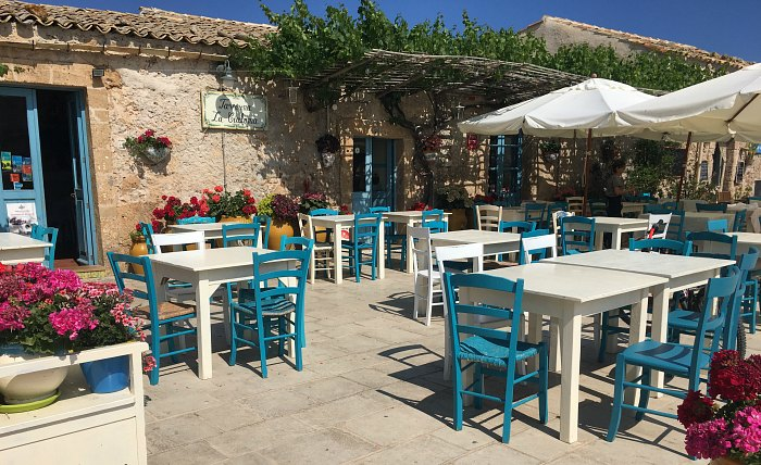 Colourful dining chairs and tables in Marzamemi's town centre