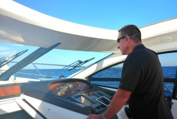 captain steering a Sunseeker yacht in the Mediterranean