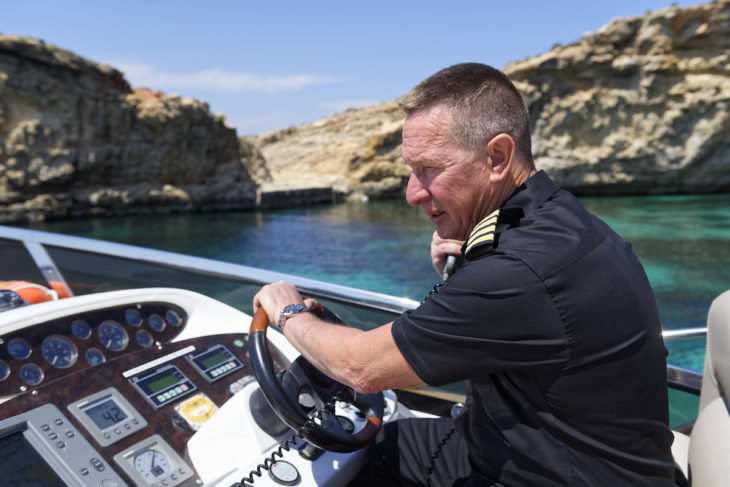 Captain on the flybridge of a Sunseeker luxury motor yacht in Malta. Sailing Terms.