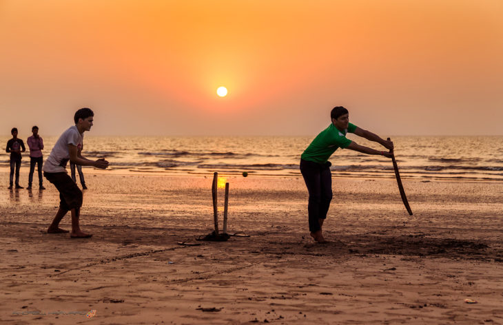 Playing cricket on a sunset beach in Mumbai, formerly Bombay (India)
